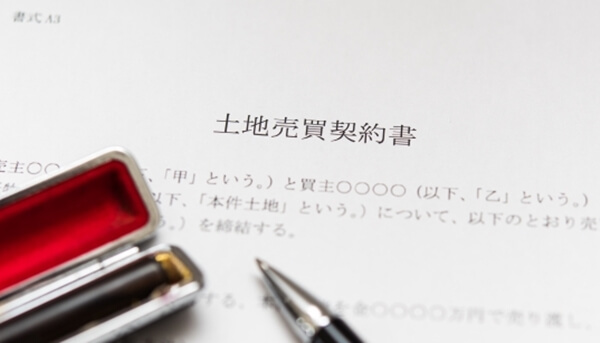 重要事項の確認語、土地売買契約書に署名・押印しているところ