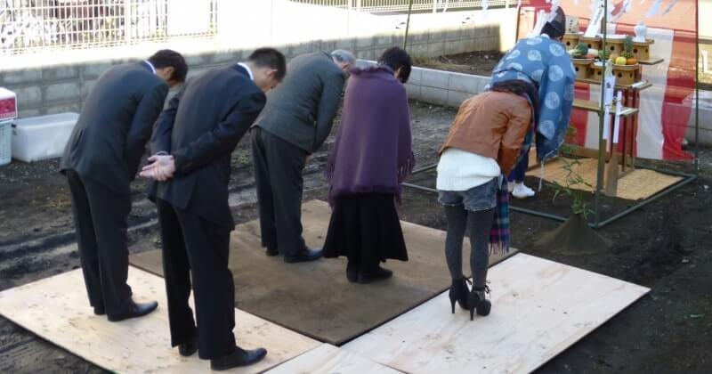 地鎮祭の一般的な服装で祭壇に向かって礼をする神主と施主・建築関係者